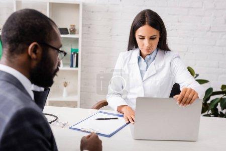 Photo pour Foyer sélectif du médecin ouverture ordinateur portable sur le lieu de travail près du patient afro-américain - image libre de droit