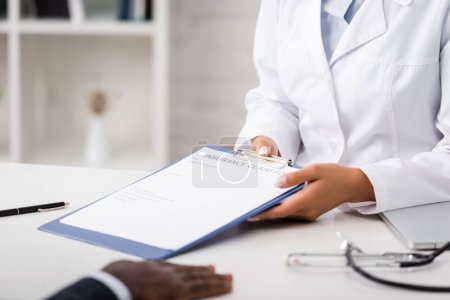 cropped view of doctor holding clipboard with insurance claim form near african american patient