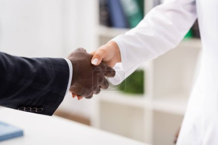 cropped view of african american patient shaking hands with doctor