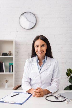 Photo pour Joyeux médecin brunette regardant la caméra tout en étant assis sur le lieu de travail près du presse-papiers avec formulaire d'assurance - image libre de droit