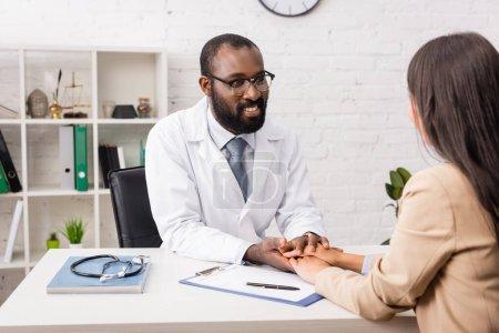Photo pour Médecin afro-américain dans les lunettes toucher les mains d'un patient brune près du presse-papiers avec formulaire d'assurance - image libre de droit