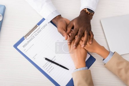 top view of clipboard with insurance claim form and african american doctor touching hands of patient