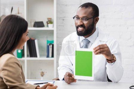 Foto de Enfoque selectivo del alegre médico afroamericano sosteniendo tableta digital con pantalla en blanco cerca de la mujer morena - Imagen libre de derechos