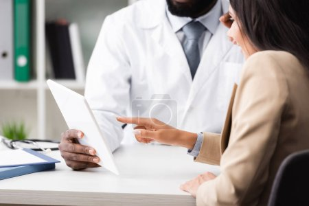 cropped view of african american doctor holding digital tablet near patient pointing with finger
