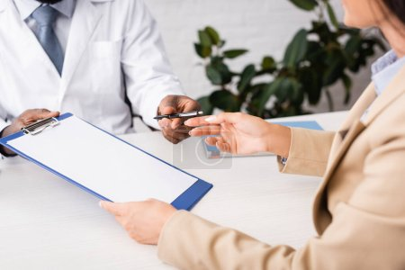 partial view of woman taking pen and clipboard with blank paper from african american doctor