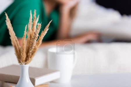 Photo pour Selective focus of spikelets, books and cup near woman in bedroom - image libre de droit