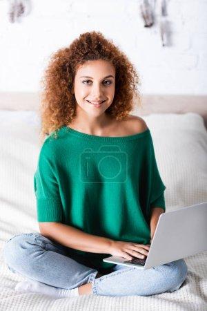 Photo pour Femme bouclée en jeans regardant la caméra tout en utilisant un ordinateur portable sur le lit - image libre de droit