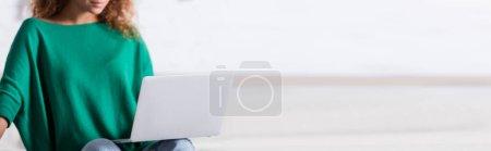 Photo pour Panoramic shot of young woman using laptop at home - image libre de droit