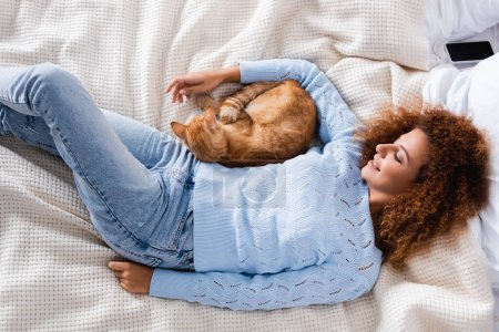 Photo pour Top view of young woman in sweater lying near tabby cat on bed - image libre de droit