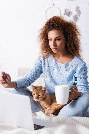 Concentration sélective de la femme tenant la tasse près du chat et de l'ordinateur portable sur le lit