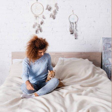Junge Frau im Pullover schaut gestromte Katze im Schlafzimmer an