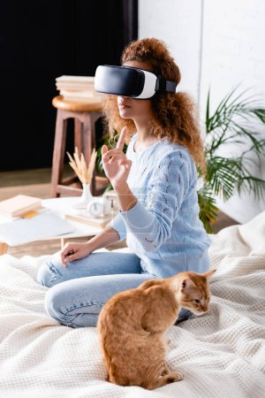 Concentration sélective de la femme en utilisant un casque de réalité virtuelle près du chat sur le lit