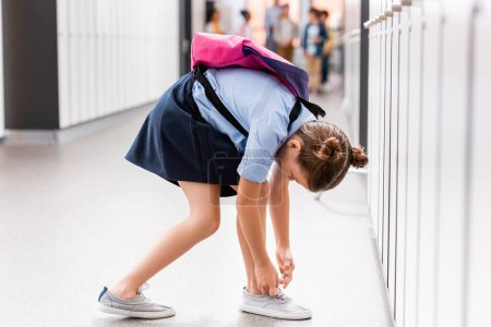 Photo for Schoolgirl with backpack tying laces on gumshoe in school corridor - Royalty Free Image