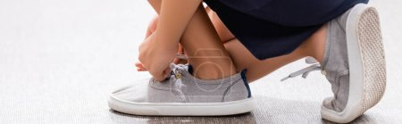 Photo for Partial view of schoolgirl tying laces on sneaker, panoramic shot - Royalty Free Image