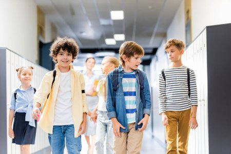 Photo for Multicultural schoolchildren walking along school corridor with teacher on background - Royalty Free Image