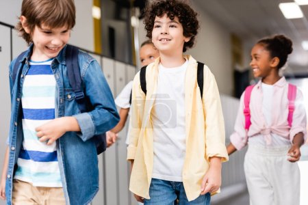 Photo for Excited multicultural schoolchildren walking along school corridor - Royalty Free Image