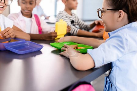 Photo for Selective focus of multiethnic classmates sitting in school eatery near lunch boxes - Royalty Free Image