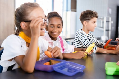 Photo for Selective focus of schoolgirl touching eyeglasses and holding fresh carrot in school canteen near multicultural friends - Royalty Free Image