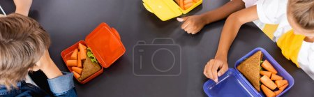 Photo for Overhead view of multicultural pupils near lunch boxes with sandwiches and fresh carrots, horizontal image - Royalty Free Image