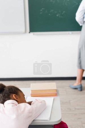 Foto de Enfoque selectivo de la colegiala afroamericana cansada durmiendo en el escritorio mientras el profesor de pie cerca de pizarra - Imagen libre de derechos