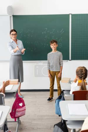 Photo for Teacher pointing with hand while standing near schoolboy and chalkboard with equations - Royalty Free Image