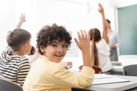 Photo pour Selective focus of arabian schoolboy with hand in air looking at camera near multicultural classmates - image libre de droit