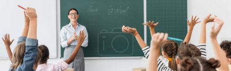 Photo for Back view of multicultural pupils with hands in air, and teacher standing at chalkboard with back to school inscription, horizontal image - Royalty Free Image