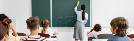 Photo for Back view of teacher writing on chalkboard near multiethnic pupils during lesson, horizontal image - Royalty Free Image