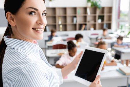 Photo pour Mise au point sélective de l'enseignant tenant une tablette numérique avec écran vierge et regardant la caméra près des élèves multiculturels en classe - image libre de droit
