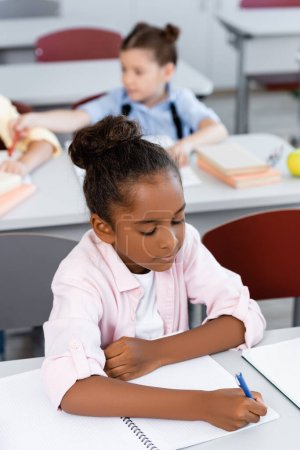 Photo for Selective focus of african american schoolgirl writing on notebook at desk in school - Royalty Free Image