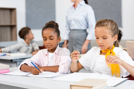 Photo for Selective focus of multcultural schoolgirls sitting near books and notebooks on desk in classroom - Royalty Free Image