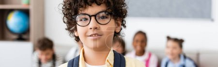 Photo pour Panoramic shot of muslim schoolboy looking at camera in classroom - image libre de droit