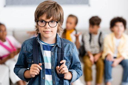Photo pour Concentration sélective de l'écolier dans les lunettes tenant le sac à dos dans la classe - image libre de droit