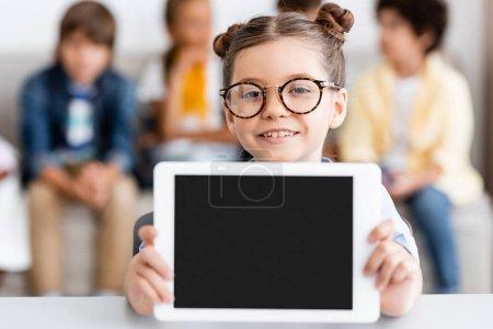 Photo for Selective focus of schoolgirl in eyeglasses holding digital tablet at desk - Royalty Free Image