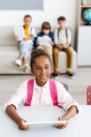 Photo for Selective focus of african american schoolgirl with backpack holding digital tablet at desk near friends in classroom - Royalty Free Image