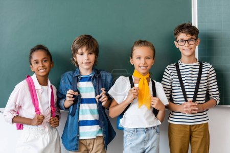 Photo for Multicultural schoolchildren with backpacks looking at camera near chalkboard - Royalty Free Image