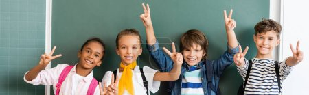 Horizontal crop of multiethnic classmates showing peace sign at camera near green chalkboard