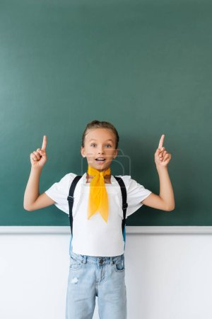 Photo for Excited schoolgirl with backpack pointing with fingers at chalkboard - Royalty Free Image