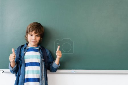 Photo for Schoolboy showing thumbs up while standing near green chalkboard - Royalty Free Image