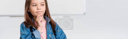 Panoramic orientation of pensive schoolgirl looking away in classroom