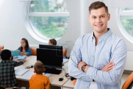 Selective focus of teacher looking at camera near schoolkids in stem school