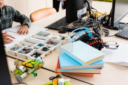 Photo pour Concentration sélective de l'écolier assis près des parties des robots et des ordinateurs à l'école - image libre de droit