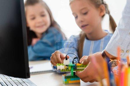Selective focus of teacher holding robot near schoolgirls and computer in classroom