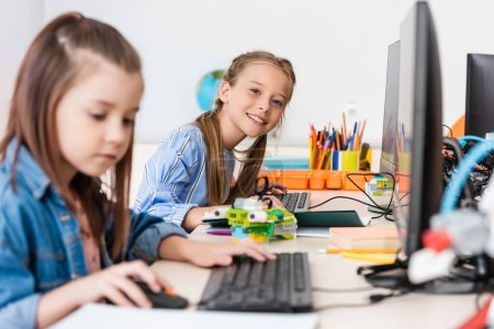 Selective focus of schoolgirl looking at camera near robot and computers during lesson in stem school