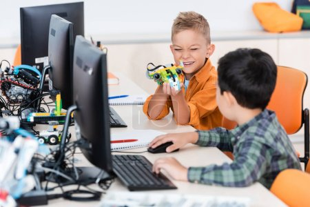 Selective focus of multiethnic schoolings playing with robot near computers in stem school