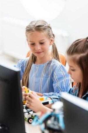 Selective focus of schoolgirls programming robot near computer in school