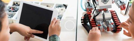 Website header of multiethnic schoolboys using digital tablet while programing robot in stem school