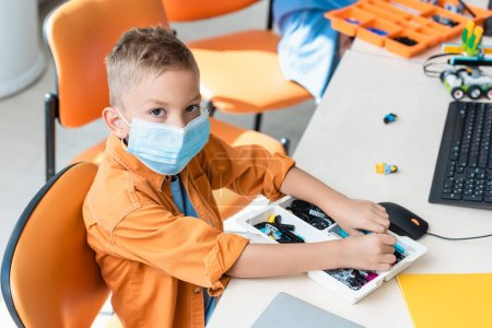 Photo for Schoolboy in medical mask holding building blocks near computer in classroom - Royalty Free Image