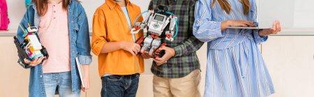 Photo pour Vue panoramique d'écoliers tenant des robots et un ordinateur portable dans l'école de la tige - image libre de droit