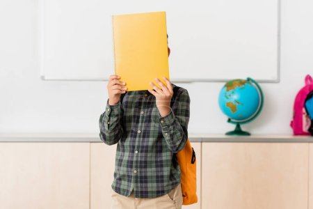 Photo for Schoolboy covering face with book in classroom of stem school - Royalty Free Image